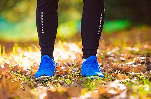 picture of a runners legs and feet standing in the park