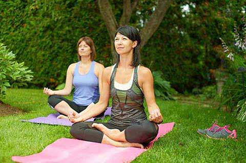 picture of two women doing Yoga in nature