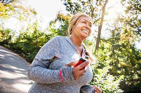 Image of a woman running in the park with a smile on her face
