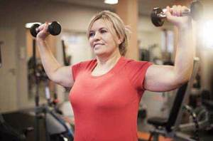 Woman lifting weights above her head while smiling