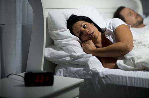 Picture of women laying in bed with a stressed look on her face