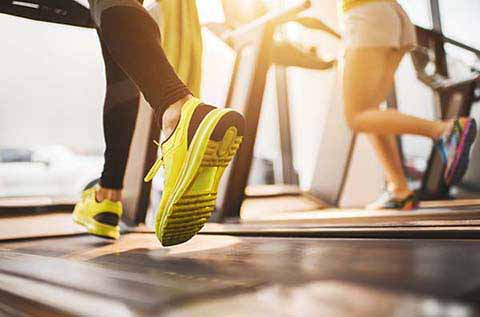 Picture of a woman's legs and feet running on a treadmill