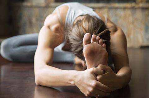 picture of a woman stretching her head down to her knee