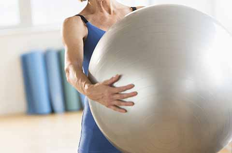 Image of a woman holding an Exercise Ball