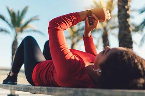 Woman checking her fitbit stats while laying on the ground