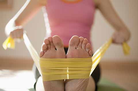 Picture of a woman pulling a resistance band from her feet