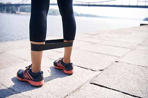 picture of a woman with a black resistance band around her calves