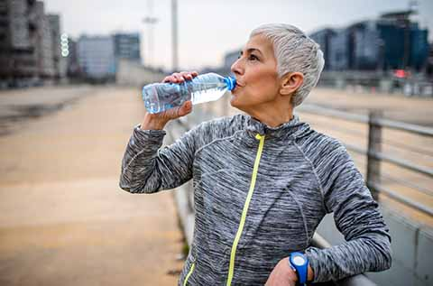 Picture of a woman drinking out of a water bottle after a workout