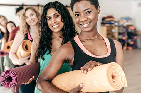 Picture of women holding Yoga mats