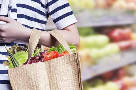 woman shopping with a reusable grocery bag